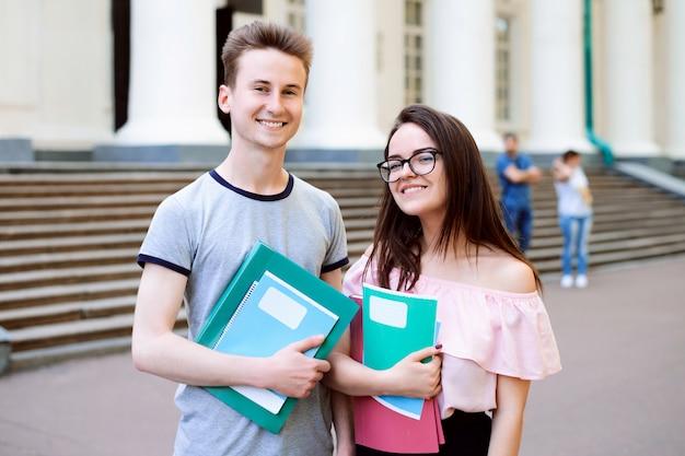 Zwei freunde, die nahes hochschulgebäude im freien mit büchern und übungsbüchern vor klassen stehen