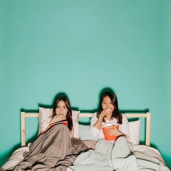 Zwei freunde, die popcorn während des interessanten films essen