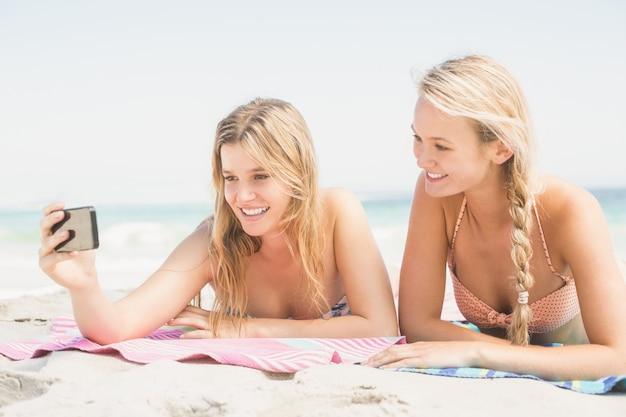 Zwei freunde, die selfie beim lügen auf dem strand nehmen