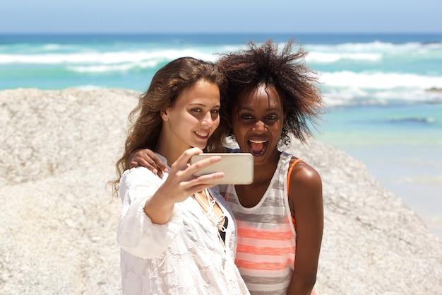Zwei freunde, die selfie mit handy nehmen