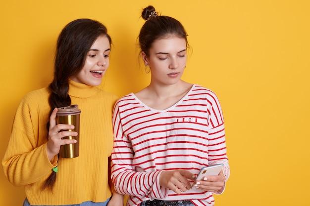 Zwei freunde, die smartphone teilen und zusammen kaffee trinken, posieren
