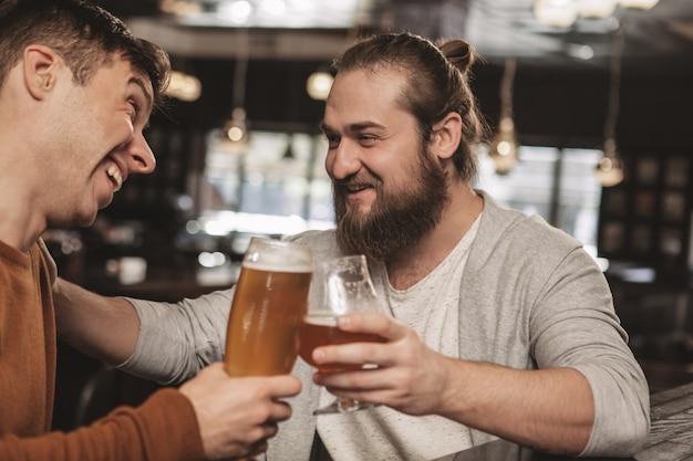 Zwei freunde, die über bier an der kneipe plaudern