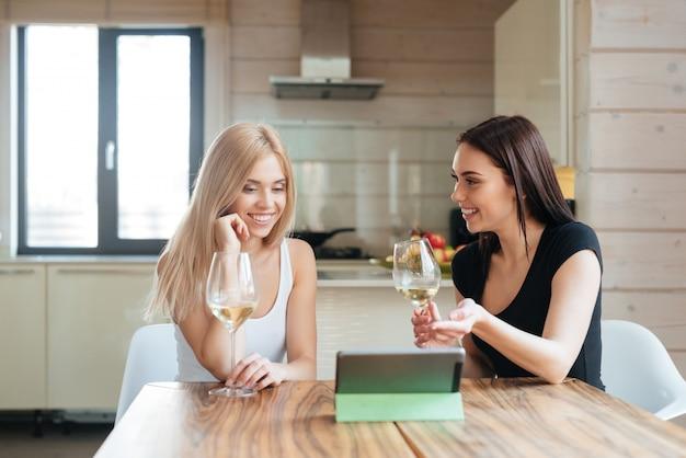 Zwei freunde, die wein trinken und tablet-computer betrachten