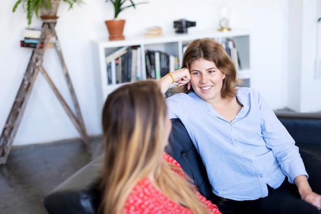 Zwei freunde, die zu hause auf einem sofa im wohnzimmer sprechen und lachen