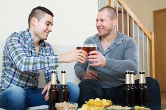 Zwei freunde, die zu hause bier trinken