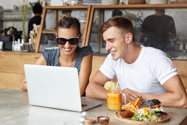 Zwei freunde, die zusammen einen laptop benutzen