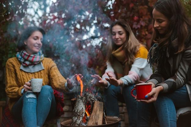 Zwei freunde entspannen sich gemütlich und trinken wein an einem herbstabend im freien am feuer im hinterhof.
