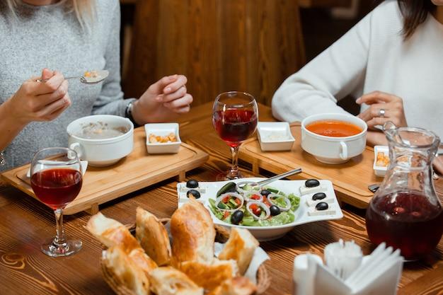 Zwei freunde essen suppe und salat, während sie kompott trinken