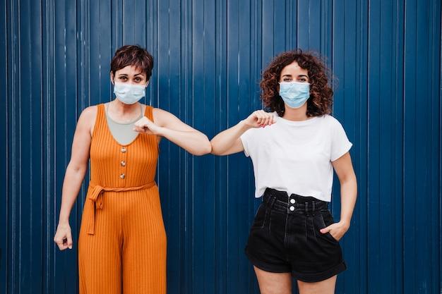 Zwei freunde frauen im freien tragen gesichtsmaske gruß mit ellbogen. konzept der sozialen distanz. pandemie während des corona-virus.