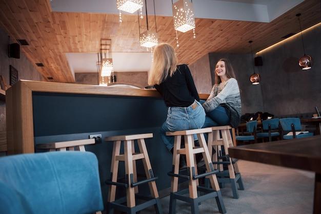 Zwei freunde genießen gemeinsam kaffee in einem café, während sie an einem tisch sitzen und sich unterhalten