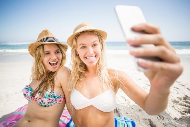 Zwei freunde im bikini, der ein selfie nimmt