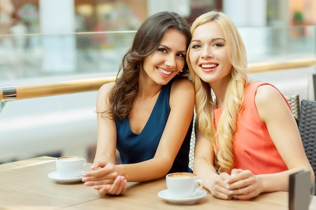 Zwei freunde im café. zwei junge freundinnen sitzen im café und schauen in die kamera