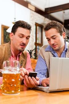 Zwei freunde in der bayerischen kneipe mit laptop