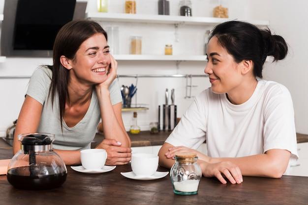 Zwei freunde in der küche unterhalten sich beim kaffee