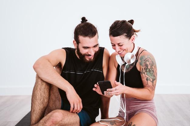 Zwei freunde in der turnhalle, die musik am handy und am kopfhörer hören und spaß haben. sport- und technologiekonzept