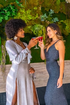 Zwei freunde in galakleidern, die einen cocktail auf einer party in einem hotel, lebensstil haben. glamour lifestyle, exklusive party