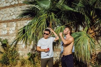 Zwei freunde, junge männer mit gläsern champagner auf dem hintergrund von tropischem grün