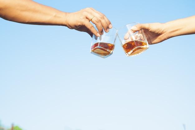 Zwei freunde klirren gläser alkoholisches getränk des whiskygetränks zusammen auf hintergrund des blauen himmels