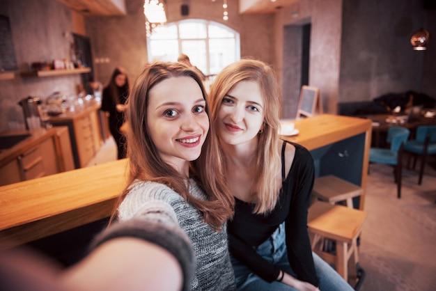 Zwei freunde machen selfies mit einem smartphone und haben spaß
