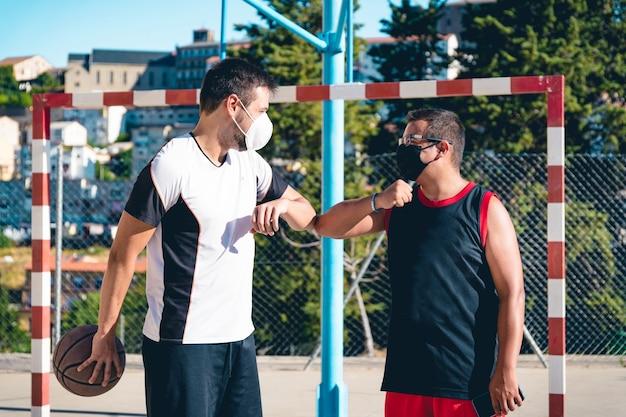 Zwei freunde mit masken begrüßen sich bevor sie anfangen basketball zu spielen