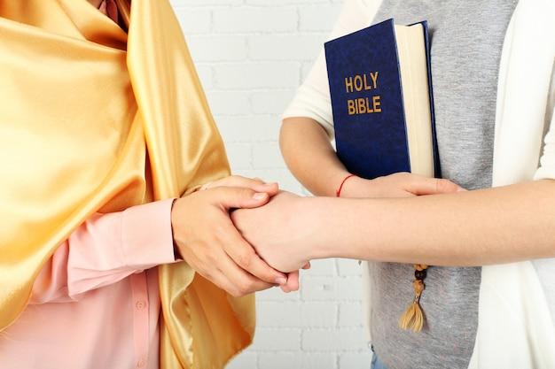Zwei freunde mit unterschiedlichen religionssymbolen