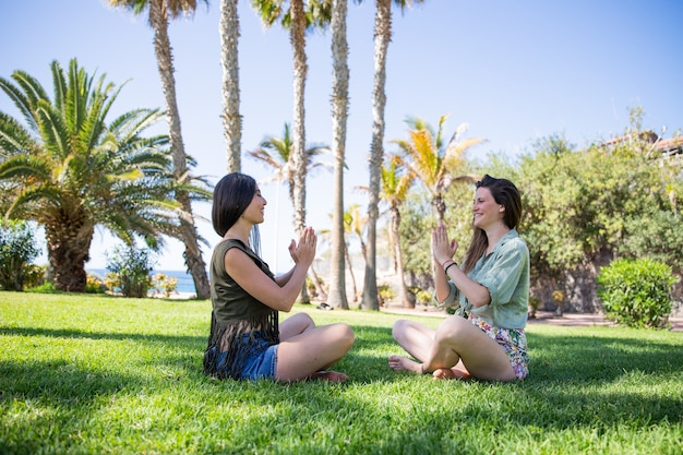 Zwei freunde praktizieren yoga in einem freiluftpark an einem wunderschönen exotischen ort. zwei freunde praktizieren yoga in einem freiluftpark an einem wunderschönen exotischen ort