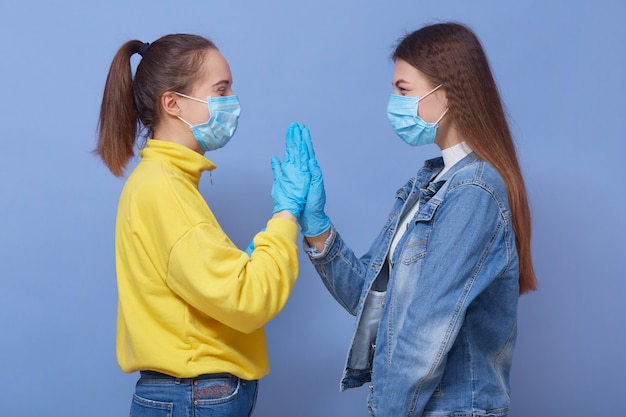 Zwei freunde sind freizeitkleidung, medizinische masken und latexhandschuhe