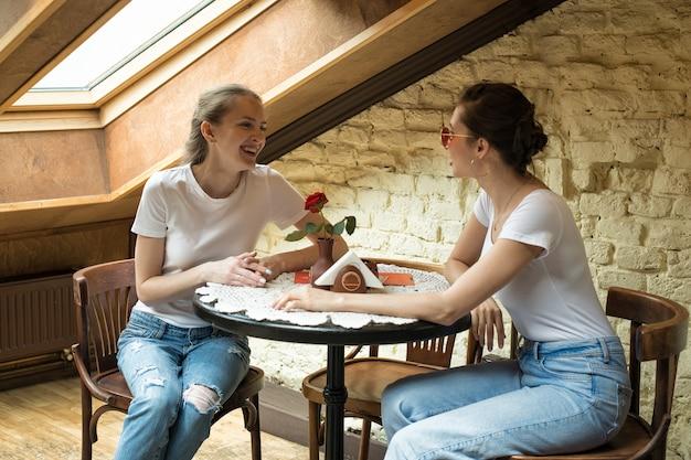 Zwei freunde sitzen am tisch und lachen. freundliches treffen, klatsch. freundschaftskonzept