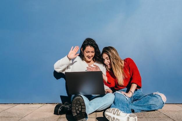 Zwei freunde sitzen auf dem boden und winken während einer videokonferenz auf den laptop-bildschirm.