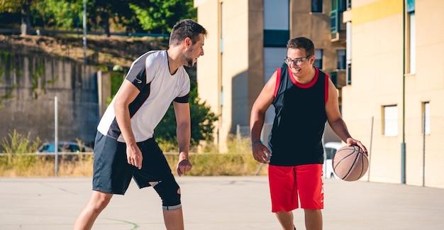 Zwei freunde spielen basketball auf einer straßenbahn