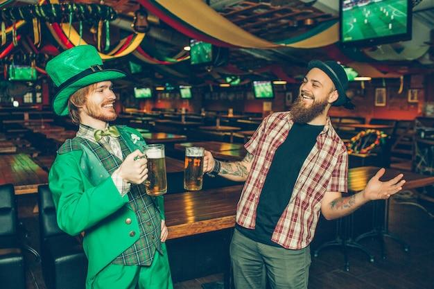 Zwei freunde stehen im kneipenlächeln. sie halten krüge bier. der typ auf der linken seite trägt patricks anzug. sie freuen sich, sich zu sehen.