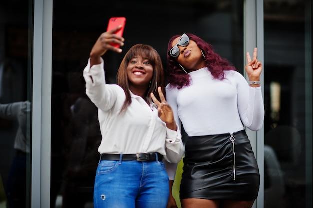 Zwei freundinnen afroamerikanische modelle posierten im freien mit handy zur hand.