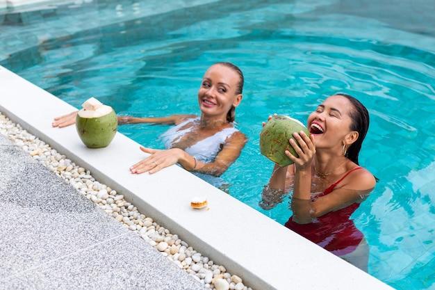 Zwei freundinnen asiatisch und kaukasisch mit make-up im schwimmbad an der villa