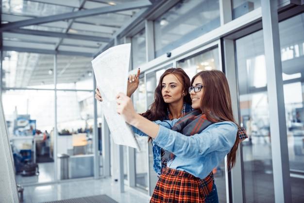 Zwei freundinnen auf der suche nach einer streckenkarte.