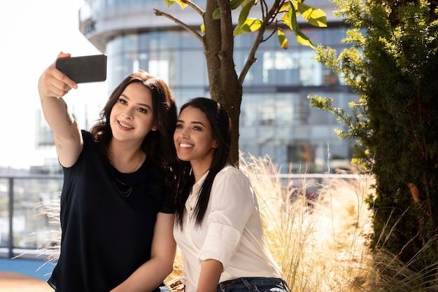 Zwei freundinnen auf einer dachterrasse machen ein selfie