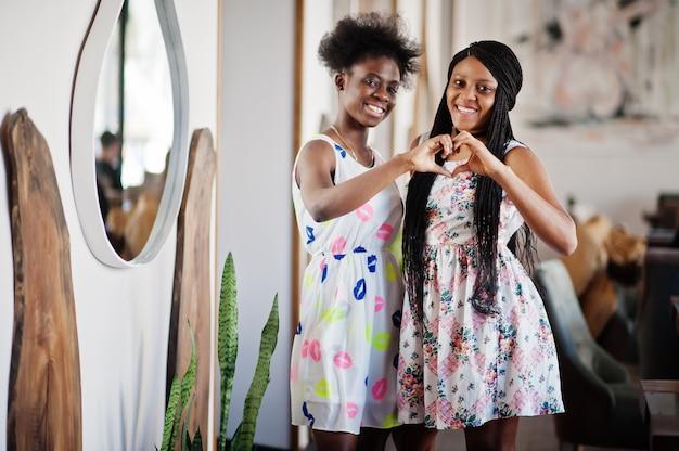 Zwei freundinnen bei sommerkleidern posieren im café und zeigen herz mit den händen