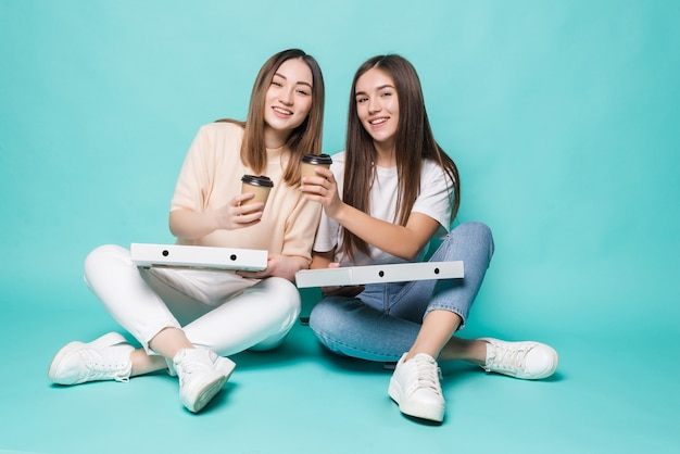 Zwei freundinnen, die auf dem boden sitzen, trinken kaffee, um pizza zu essen, die auf türkisfarbener wand isoliert ist