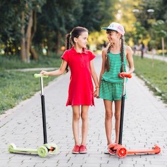 Zwei freundinnen, die auf gehweg mit ihren stoßrollern stehen