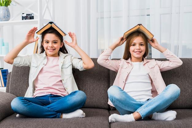 Zwei freundinnen, die auf grauem sofa mit buch über ihrem kopf sitzen