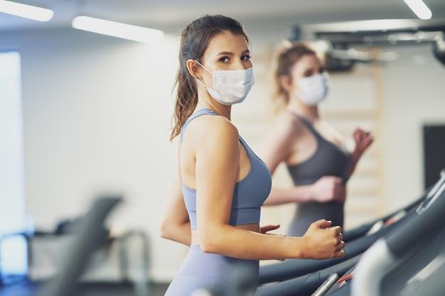Zwei freundinnen, die aufgrund von covid-19 auf dem laufband in masken trainieren