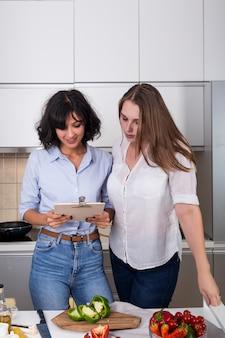 Zwei freundinnen, die das rezept in klemmbrett bei der zubereitung des lebensmittels lesen