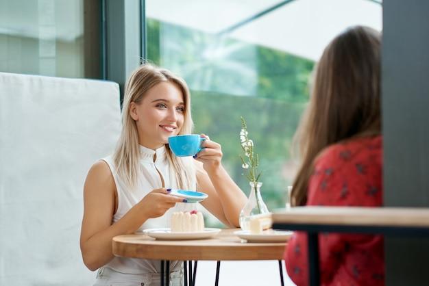 Zwei freundinnen, die den kaffee, sprechend trinken.
