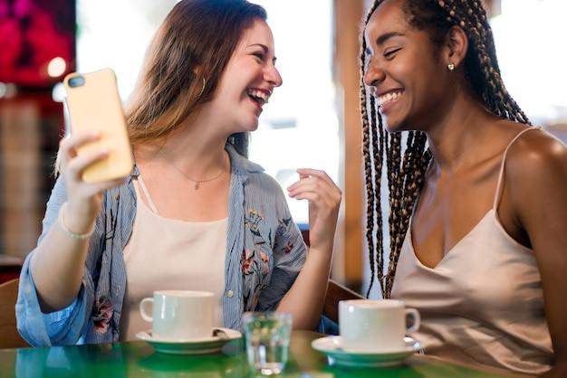 Zwei freundinnen, die ein mobiltelefon benutzen, während sie zusammen eine tasse kaffee in einem café trinken. freunde-konzept.