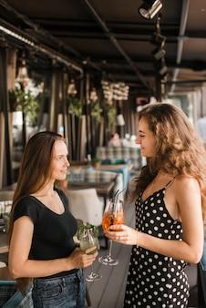 Zwei freundinnen, die einander halten getränke betrachten