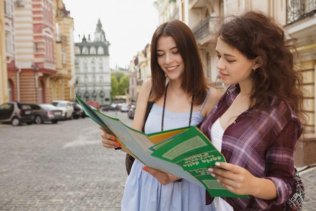 Zwei freundinnen, die eine karte, besichtigung in einer alten stadt verwenden, kopieren raum