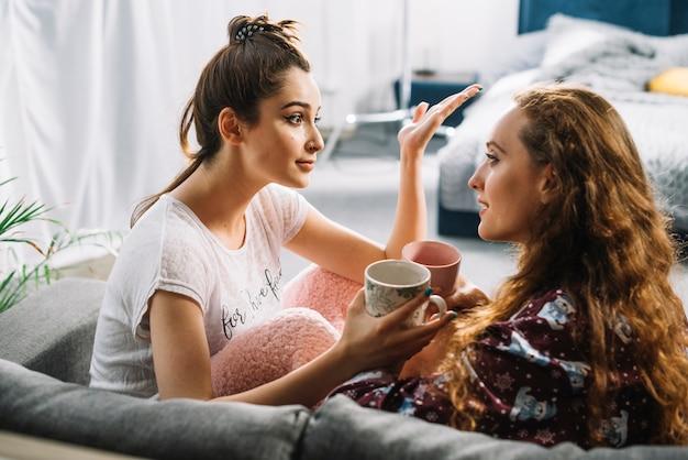 Zwei freundinnen, die gespräch beim trinken des kaffees haben