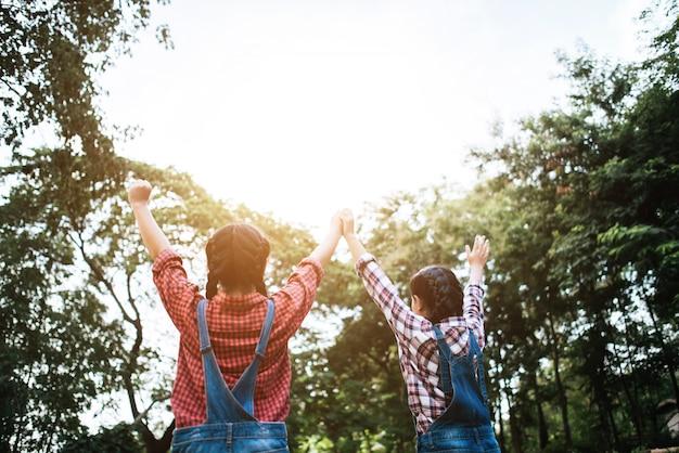 Zwei freundinnen, die hände halten und hochgehalten werden.