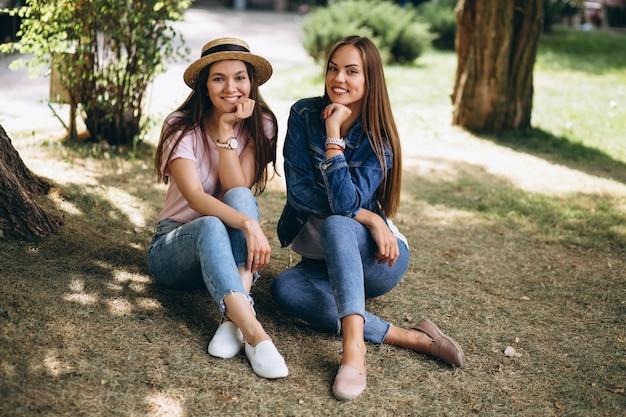 Zwei freundinnen, die im park sitzen