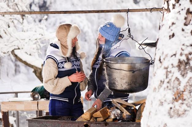 Zwei freundinnen, die in der winte natur auf einem feuer im kessel kochen. mädchen aalen sich im feuer im winter.