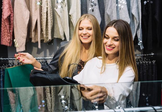 Zwei freundinnen, die kleidung im shop betrachten